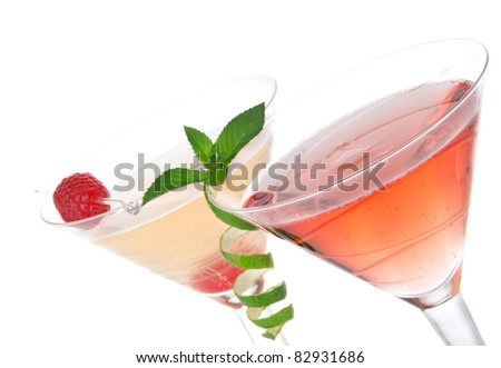 Martini alcohol cocktails in row  tequila sunrise, garnished with raspberry, lime, mint in martinis cocktail glasses on a white background - stock photo