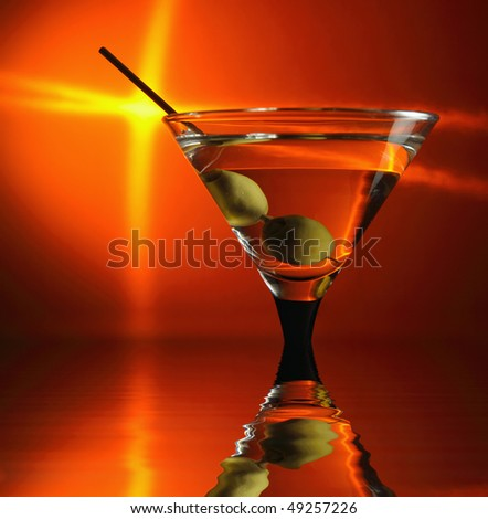 martini and green olives in wineglass,focus on a olives
