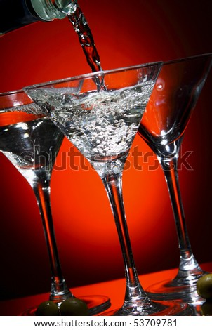 Martini being poured into a glass  over red - stock photo