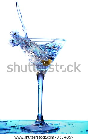 Martini being poured into a glass (toned in blue) - stock photo