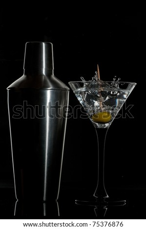 martini cocktail and a shaker on a black background