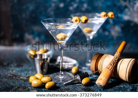 Martini cocktail drink with olives garnish and tools on rusty background - stock photo