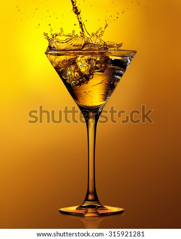 Martini cocktail with splash against a gold background