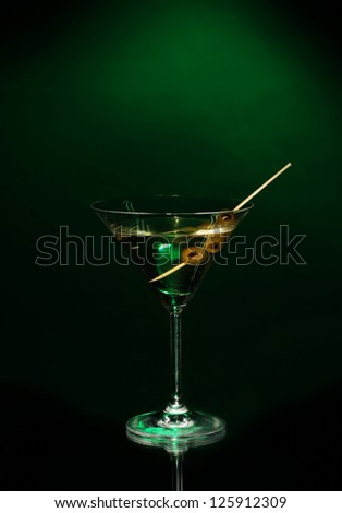 Martini glass and olives on dark background - stock photo