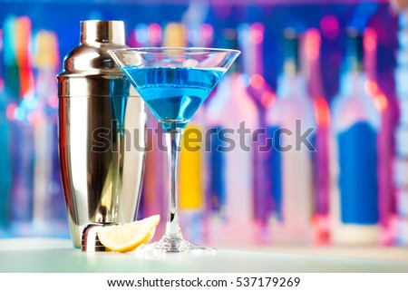 Martini glass and shaker standing on a bar counter