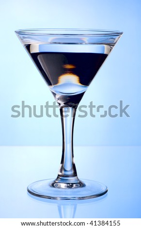 Martini glass with beverage on blue background with reflection