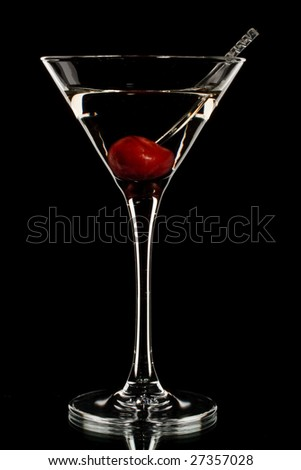 Martini glass with cherry isolated on a black background. - stock photo