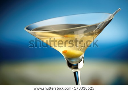 Martini glass with green olive, sea on the background