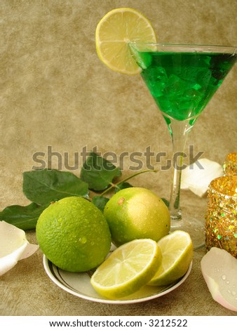 Martini glass with limes on a plate and candles