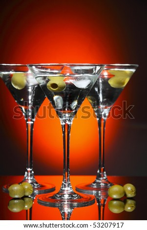 Martini glass with olive inside over red