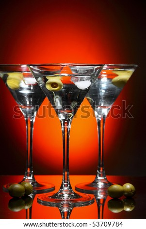 Martini glass with olive inside over red - stock photo
