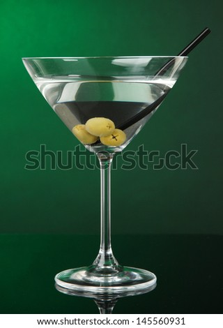 Martini glass with olives on dark green background - stock photo
