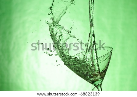 Martini glass with stream fresh drink. Splashing cocktail