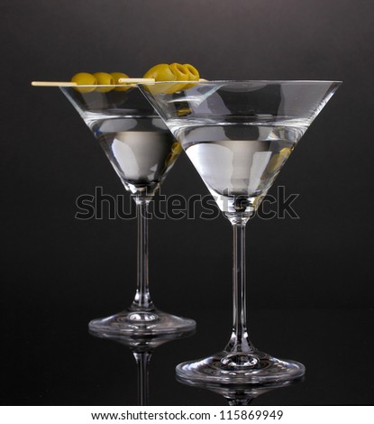 Martini glasses and olives on grey background - stock photo