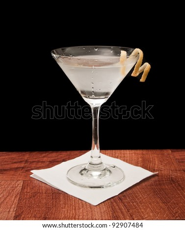 Martini on a bar garnished with a lemon twist isolated on a black background - stock photo