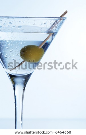 Martini with an olive on a light background