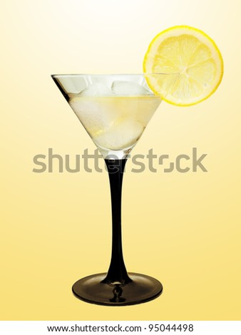 Martini with lemon and ice on a yellow background
