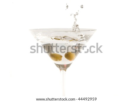 Martini with olive splash, against white