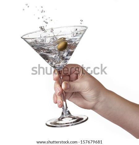Martini with splash and olive in woman hand isolated on white - stock photo