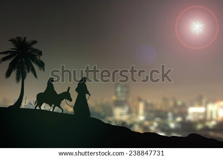 Mary and Joseph with a donkey on Christmas Eve. Cities in the 21st Century  on background. Nativity story. - stock photo