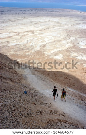 MASADA,ISR - OCT 21:Visitors climbing down Masada Fortress in Israel by using the steep ancient snake path on Oct 21 2006.Masada considered as one of the most popular tourist destination in Israel. - stock photo