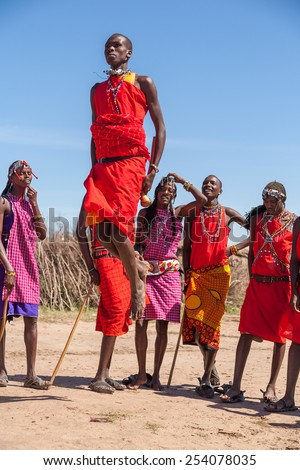 MASAI MARA,KENYA, AFRICA- FEB 12: Masai warriors dancing traditional jumps as cultural ceremony,review of daily life of local people,near to Masai Mara National Park Reserve, Feb 12, 2010,Kenya - stock photo