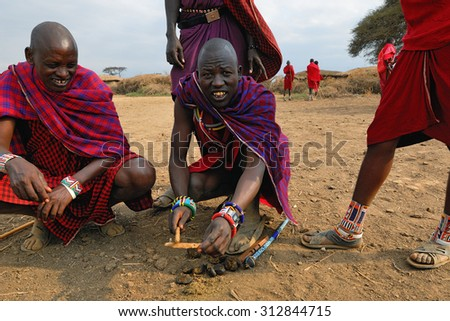 MASAI MARA, KENYA - AUG 23, 2010: An unidentified men from Masai tribe showing how they make fire in a traditional way from donkey droppings to guests visiting their village - stock photo