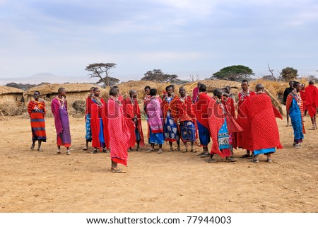 MASAI MARA, KENYA - AUGUST 23: Group of unidentified African women from Masai tribe prepare to show a traditional Jump dance on August 23, 2010 in a local village near Masai Mara National park, Kenya - stock photo