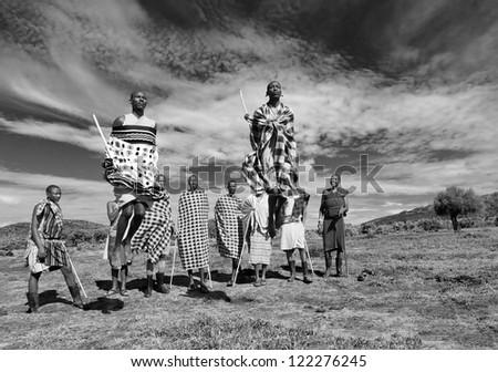 MASAI MARA, KENYA - DECEMBER 2: Masai warriors dancing traditional jumps as cultural ceremony. As well as women sing and dance. Masai Mara National Park, December 2, 2011 in Kenya - stock photo