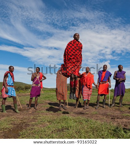 MASAI MARA, KENYA - DECEMBER 2: Unidentified Masai warriors dance and participate in  traditional jumps as part of a cultural ceremony on December 2, 2011 in Masai Mara National Park, Masai Mara, Kenya. Women also take part in the event. - stock photo