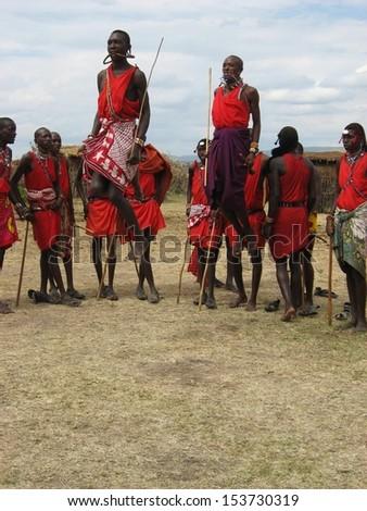 MASAI MARA, KENYA - JULY 16: Masai warriors dancing traditional jumps at cultural ceremony on July 16, 2010 in Masai Mara, Kenya. Maasai are a Nilotic ethnic group of semi-nomadic people. - stock photo