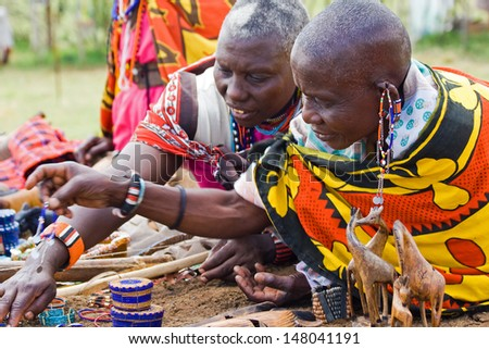 MASAI MARA, KENYA - JUNE 29: Two unidentified elderly Masai women with traditional jewelry sell their homemade souvenirs in the village on June 29, 2013 in Masai Mara.