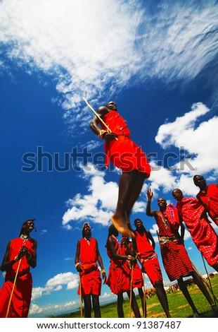 MASAI MARA, KENYA - NOVEMBER 12:  Group of African Masai warriors dance traditional jumps as cultural ceremony on November 12, 2008 in tribal village near Masai Mara National Park Reserve, Kenya. - stock photo