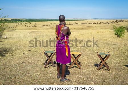 Masai warrior observing the wildebeest in Kenya, Africa - stock photo
