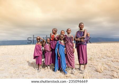 Masai woman and a children in the African savannah, looking at camera.Tanzania - stock photo