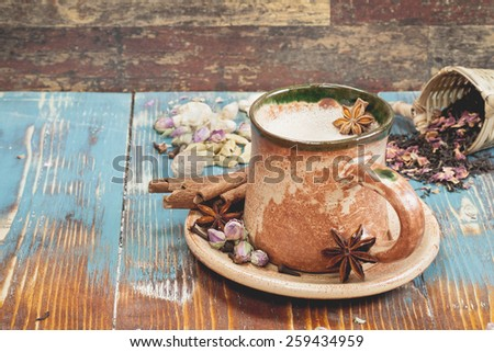 Masala chai.  Indian masala chai tea with spices and milk on rustic background. Macro, selective focus - stock photo