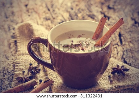 masala chai tea with spices and star Anise, cinnamon stick, peppercorns, on sack and wooden background - stock photo