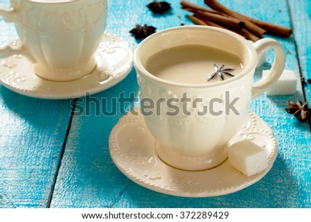 Masala spices (ginger, cloves, pepper, cinnamon, cardamom, star anise) on a wooden table - stock photo