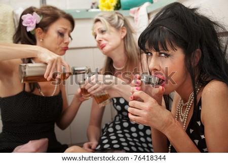 Mascara-smeared, drunk, sobbing women on kitchen floor - stock photo