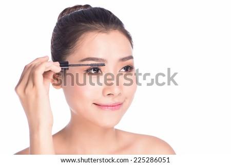 Mascara woman putting makeup on eyes. Asian female model face closeup with eye brush on eyelashes.  - stock photo