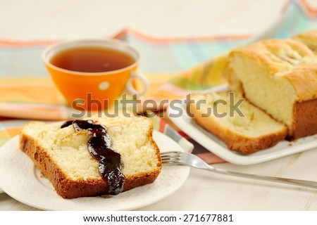 Mascarpone cake slice, cup of tea in orange teacup, blueberry jam on white bright background - stock photo