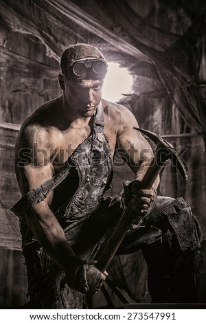 Masculine dirty coal miner with a pickaxe over dark grunge background. Mining industry. Strength. Bodybuilding.