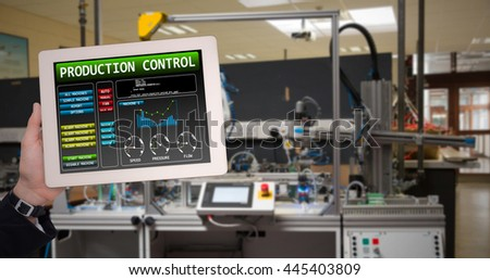 Masculine hand holding tablet against image of machinery