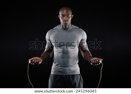 Masculine man skipping rope in dark. Portrait of muscular young man exercising with jumping rope on black background - stock photo