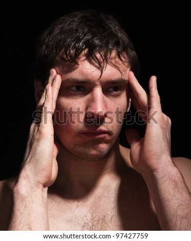 masculine problems.portrait of man on a black background.headache.