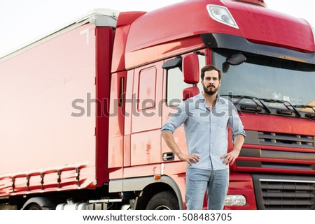 masculine truck driver standing in front of his car outside and looking with confidence at camera