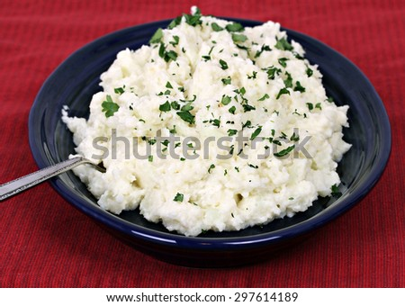 Mashed cauliflower, a popular replacement for potatoes, on a blue dish garnished with fresh parsley snips. - stock photo