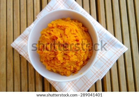Mashed cooked sweet potatoes in a bowl on wood background - stock photo