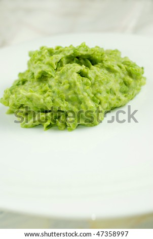 Mashed pea and potato on white plate with selective focus - stock photo