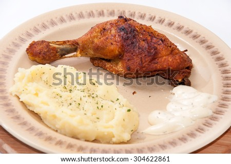 Mashed potato and fried chicken drumsticks. - stock photo
